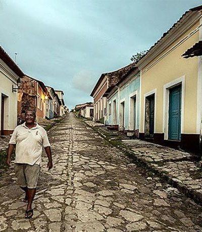 Quilombola camina por calle empedrada y solitaria en Brasil.