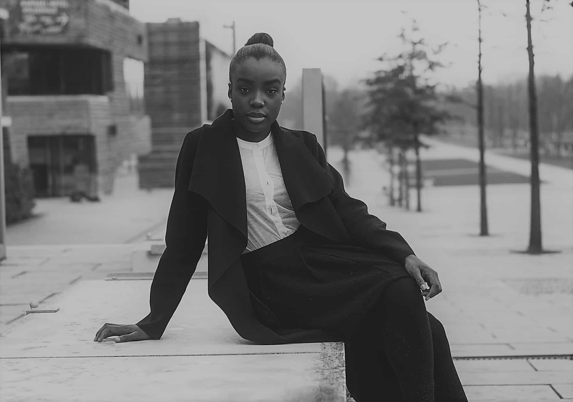 Mujer afro vestida elegantemente, sentada sobre una banqueta en la calle de una ciudad.