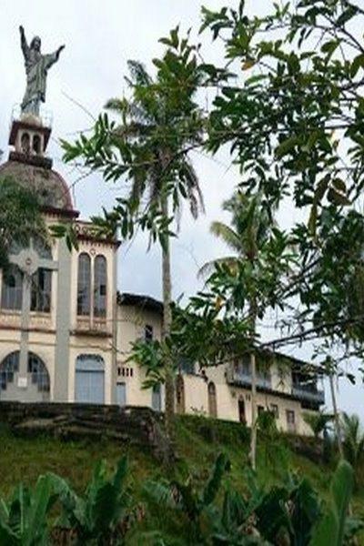 El templo católico de Puerto Merizalde con su cristo visto detrás de árboles y palmas.