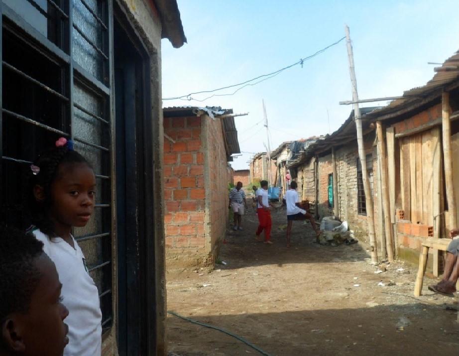 Paisaje de Brisas de Comuneros en 2014; una niña afro mira la cámara mientras unos jóvenes juegan en el fondo.