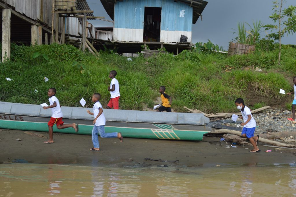 Niños corren por la ribera del río junto a canoas al paso de la Caravana por una de las comunidades visitadas