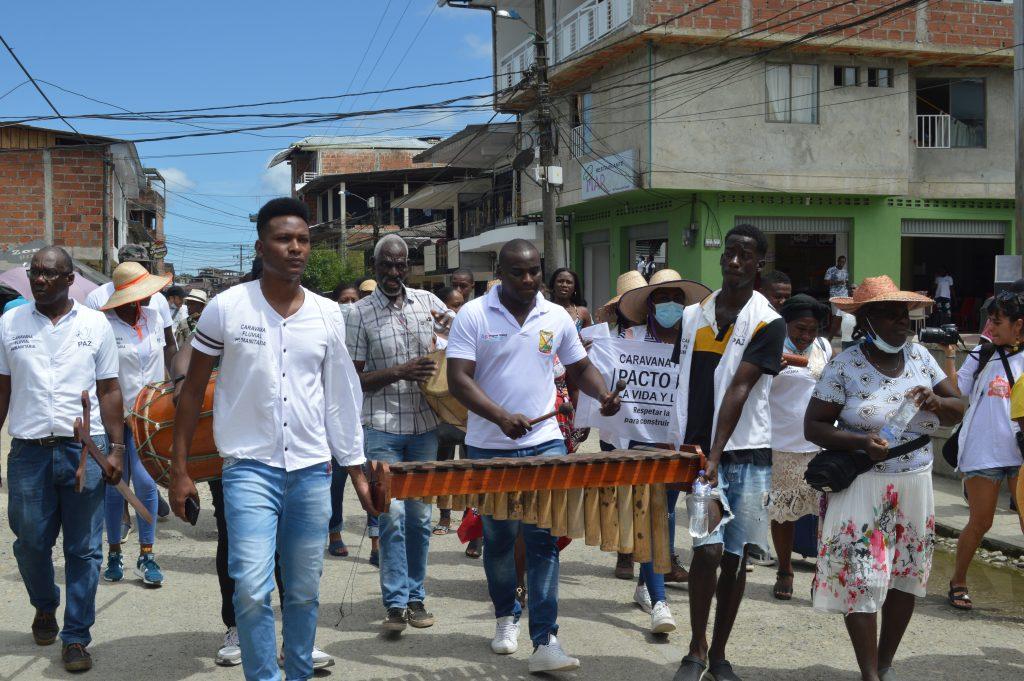 Dos jóvenes sostienen una marimba para que se pueda tocar en una de las marchas por las comunidades en apoyo al Pacto por la Vida y por la Paz.