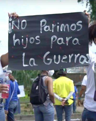 """Una mujer y una joven afro en una marcha sostienen un letrero que dice """"NO parimos hijos para la guerra"""""""